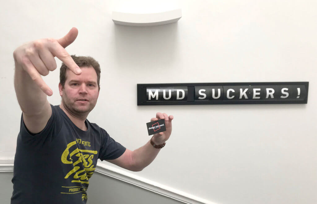 "Steven doing a gansta stance beside a sign which reads ""mud suckers!"""